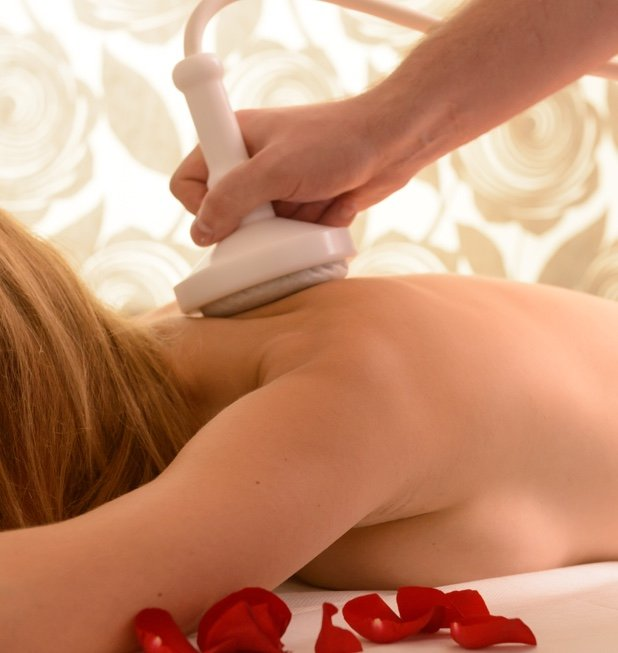 Woman lying on massage bed, with rose petals having a massage by electric massage wand